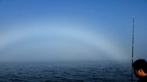 Gray rainbow at sea.